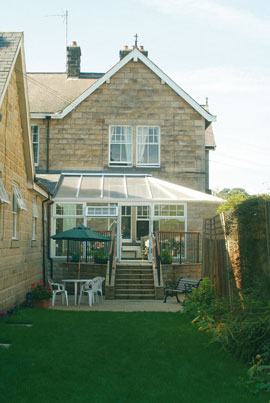The rear of Ashhcroft House showing the conservatory and patio