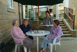 Ashcroft House residents and staff sat talking outside at a patio table